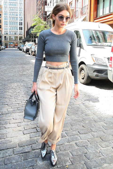 Gigi Hadid looks great in baggy high waisted chinos, a crop top, metallic oxfords, and a Michael Kors Collection bag. Purchase her COS trousers, $69,from cosstores.com.