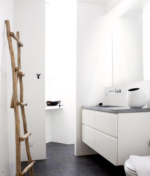 minimalistic style . grey white black . fixtures . large mirror . grey top . black floor . 'door' to shower .