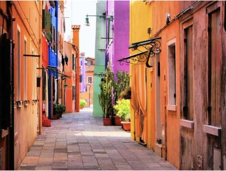 Imagine a kitchen sink stuck on a wall without a window. This wallpaper gives the illusions of having a window open to a colorful street view in Burano, Italy. #Wallpaper, #ItalianView, #Kitchen, #WallDecor