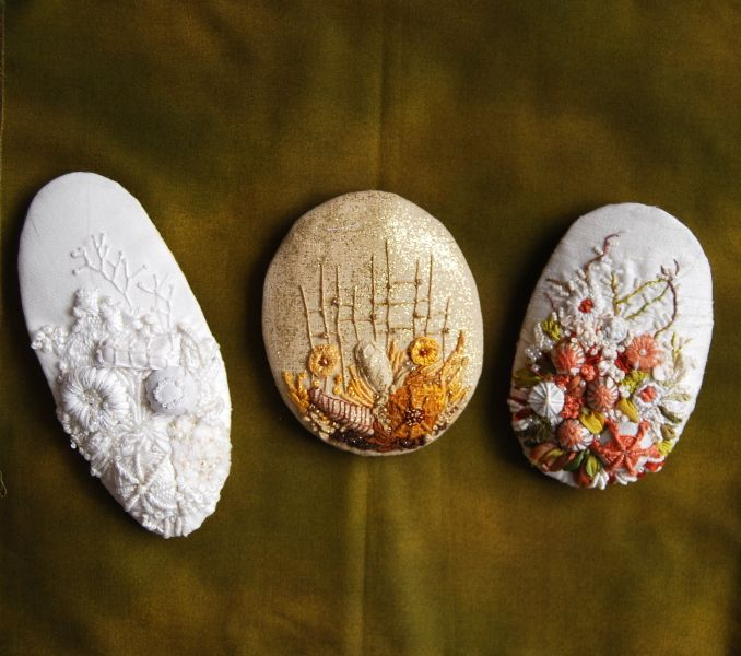 Embroidered fabric covered pebbles...I think. They look lovely!