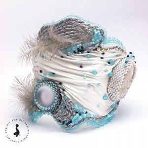Bajkowa bransoletka na jedwabiu SHIBORI, w technice haftu koralikowego, przedstawiająca postać anioła. Wykonana z kaboszonu fimo, oraz Luna Soft, sznurka do soutachu, koralików Toho i Fire Polish, koralików Miyuki Delica, taśmy cyrkoniowej, oraz prawdziwego puchu. Podszyta i wykończona białą skórką ekologiczną. Miękka i lekka – wspaniale układa się na nadgarstku, jednocześnie trzymając formę. Zapinana na guzik i pętelkę. Idealny prezent na każdą okazję: urodziny, imieniny, walentynki, inne
