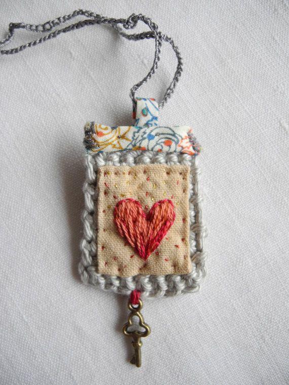 Tela teñida de corazón bordado a mano. Cosido a la luz del ganchillo gris, adornado con un trozo de tela de Liberty. Tiene un encanto clave. Mide
