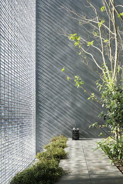 glass block wall facade enclosing courtyard . Optical Glass House . Hiroshi Nakamura & NAP Co . Hitroshima, Japan