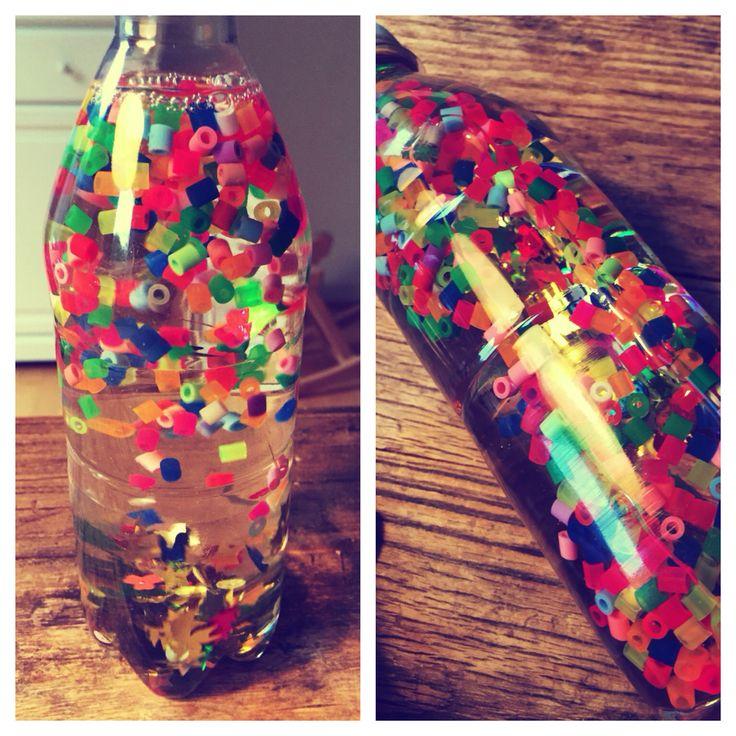 Så har jeg også prøvet at lave det nemmeste, billigste og mest farverige legetøj til sønnike. En plastflaske med perler, palietter og vand...