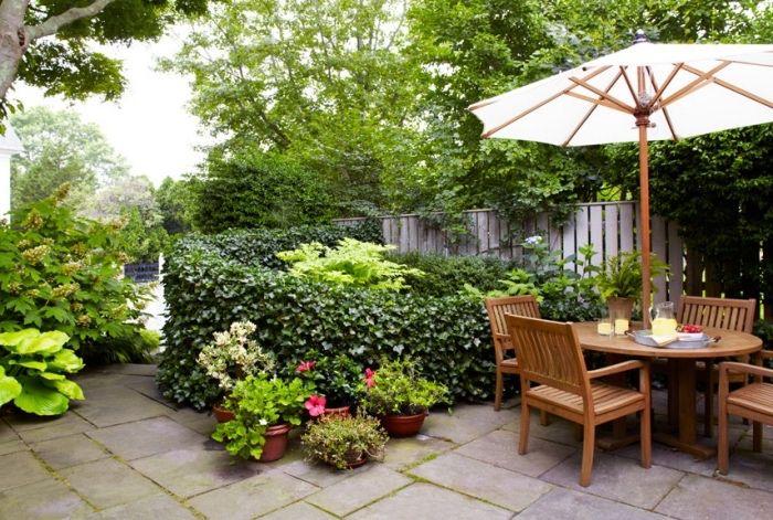 amenagement jardin avec patio de dalles de béton, chaises et table en bois, parasol, buis et pots de fleurs, palissade en bois