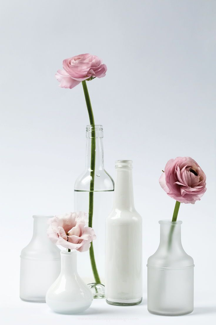 Scandinavian style photo with pink flowers in a minimal white and transparent vase arrangement.