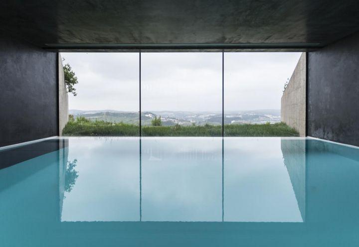 La piscina, in un tutt'uno con il paesaggio. Le pareti dipinte di scuro amplificano il senso di intimità di questo ambiente