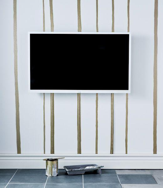Une décoratrice utilise de la peinture dorée pour camoufler les câbles qui courent le long du mur.