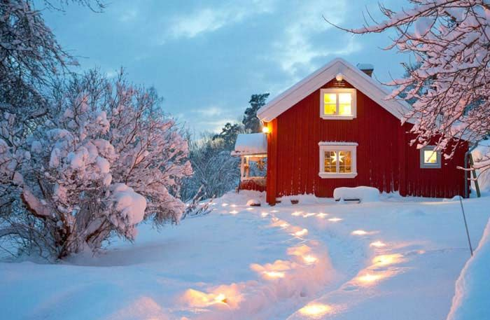 Lighted path to a red Scandinavian cabin on a snowy evening.