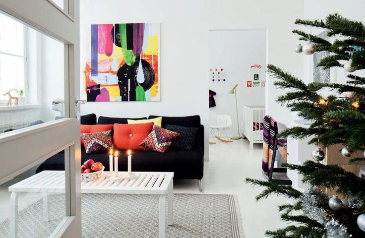 Hillitysti koristeltu joulukuusi ja punaiset omenat tuovat joulumieltä. Missoni Homen ja Hayn koristetyynyt sekä Marimekon kankaasta pingoitettu taulu antavat väriä. Sohvapöytänä on Artekin ritiläpenkki. Lattialla on Tikaun villamatto. Tammiparketti on maalattu Betoluxilla valkoiseksi | KUTKUTTAVA JOULUN ODOTUS | Koti ja keittiö
