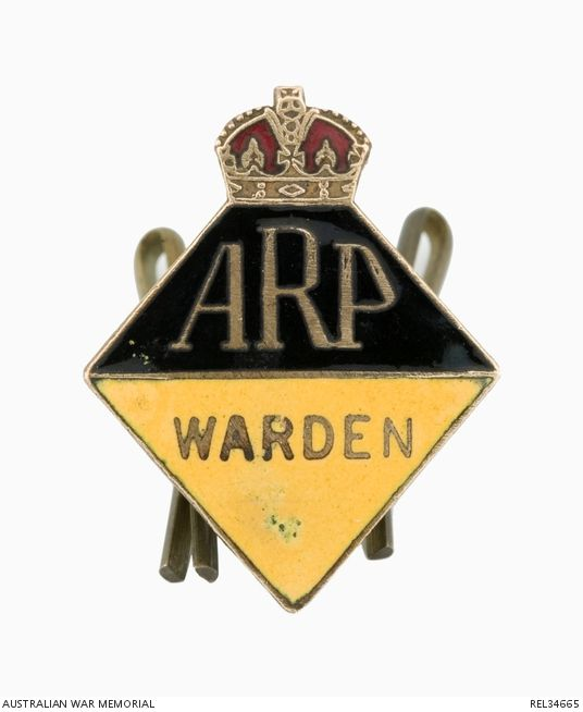 Diamond shaped brass badge with an enamel finish. The diamond is surmounted by the King's Crown and is divided horizontally into black over yellow. The letters ARP appear in the top half; the name WARDEN in the lower half; both in natural brass. The reverse is impressed '7283' and includes the maker's name and location and a pair of loop attachments.
