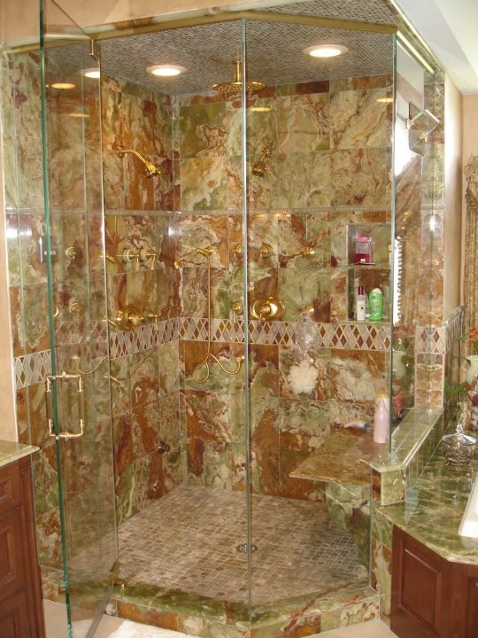 Steam shower with green onyx tiles, glass to ceiling door, and gold  fixtures.