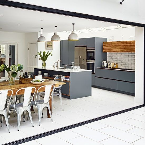 What's not to love about this sleek grey kitchen complete with island units and rustic table