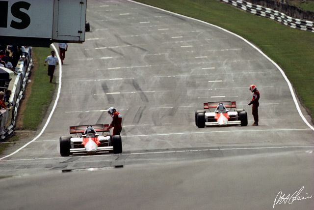 When Jonathan Palmer crashed on the 12th lap of the 1984 British GP, the race was stopped. Alain Prost and Niki Lauda were way in the lead. They came to the start:finish line, stopped, and got out of their cars before any other driver arrived. Meanwhile, Paul-Henri Cahier was crossing the track, and caught this studio scene from the corner of his eye, aimed the Canon 500 mm lens, and shot the last Kodachrome frame on his roll of film...