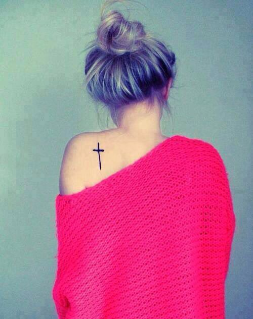 Cross tattoo on the shoulder.