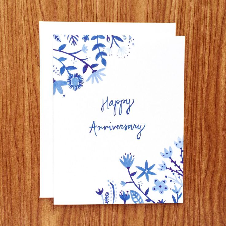 "An anniversary card for the love birds. This card features hand-painted flowers in shade of blue and ""Happy Anniversary"" hand-lettered in blue. Available as a single card paired with a 100% recycled w"