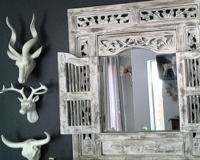 White animal heads with morrocan white wooden mirror on black walls