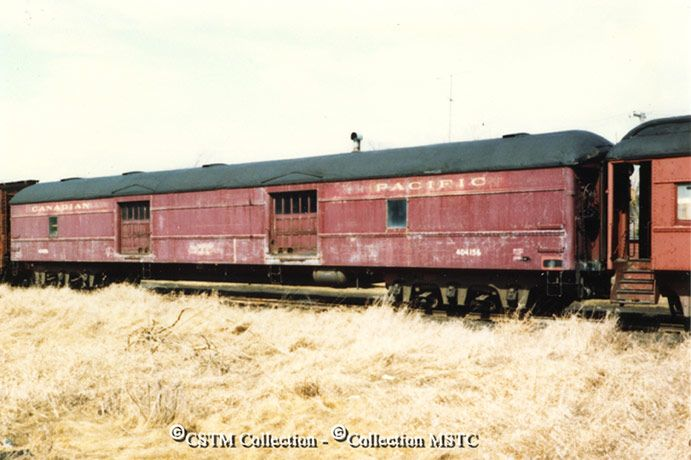 """Photo Number:  MAT001155  Photographer:  unknown  Location:  Carleton Place, ON  Railway Name:  CANADIAN PACIFIC RAILWAY CO.  Date:  1983-04-00  Caption:  """"Two cars (one a baggage car), that used to be resplendent in their Tuscan red colour on the premier trains of yesterday, are now in Carleton Place.""""  Subject:  Equipment, passenger  Equipment Number:  404156  Collection:  Mattingly"""