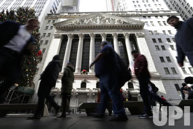Pedestrians walk by the New York Stock Exchange near Wall Street in New York City on December 27, 2016. The Dow Jones Industrial Average is…