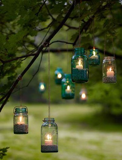 DIY tealights in jam jars suspended from a tree - lovely!