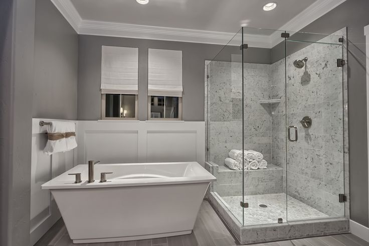 Free standing tub with wainscoting accentuate the stone surround shower walls in this brilliant owner's bath.