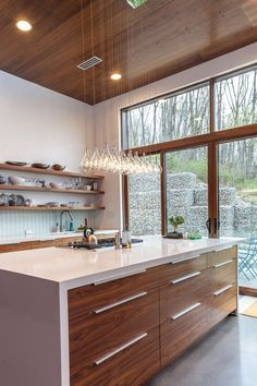 ikea kitchen furniture and white wood and light bulbs suspended above the central island