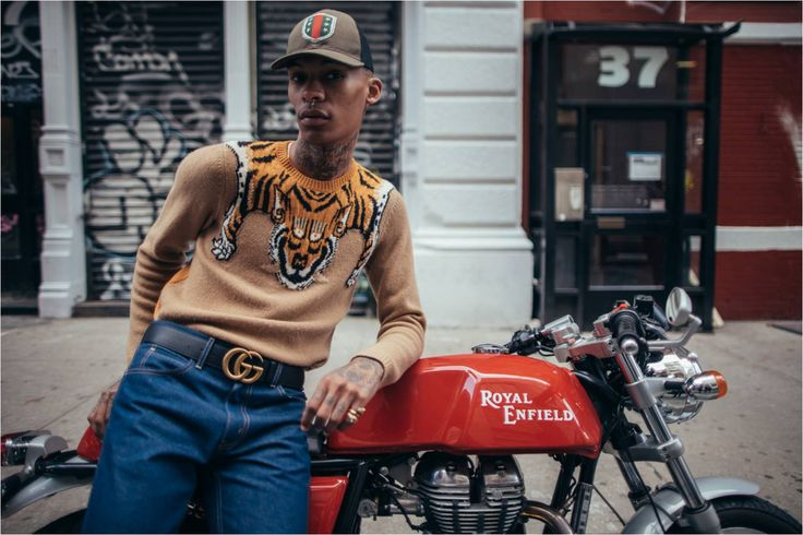 A look from the men's Gucci Cruise 2016 collection; a wool sweater with tiger detail, blue denim 5-pocket wide pants, a black leather double G buckle belt, and a hat with web crest and stars. Photo Credit: HypeBeast