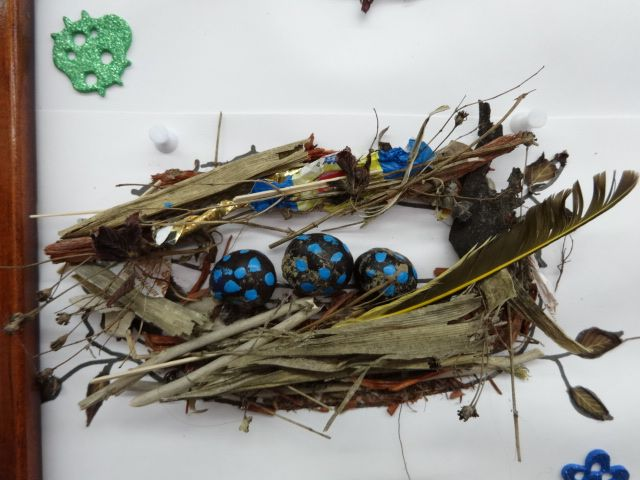 Painted rock eggs, glued to a background with twigs and feathers.
