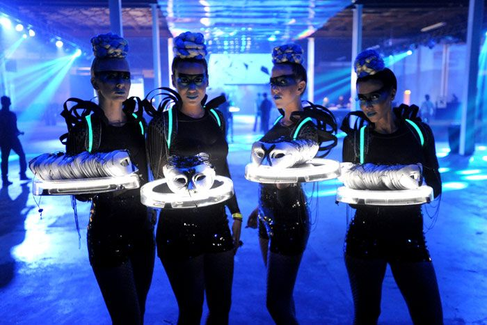 Event Staff - Futuristic models offered masquerade masks to guests at the entrance.
