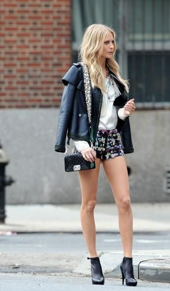 Poppy Delevigne in printed shorts, leather jacket, & high-heeled booties.