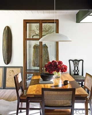 In the dining room, the Danish rosewood table, cane-back chairs, and enameled pendant light are vintage; the Art Deco teak cabinet is from Indonesia.