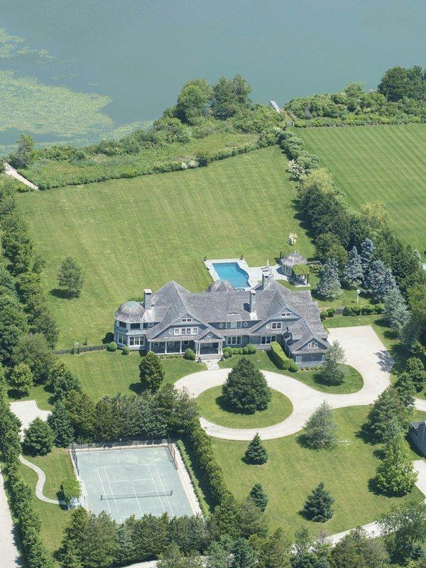 This Hamptons Estate has gabled roofs, porches, a domed sunroom, pool, tennis court, circular drive and amazing views of the water.