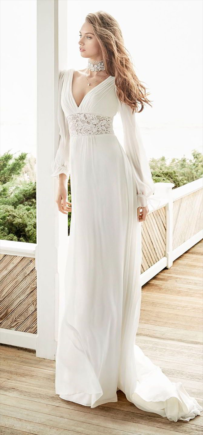 Ivory Crinkle Chiffon A-line bridal gown. V-neckline with long sleeve and open criss-cross back. Sheer lace panel with pom trim accents at waist.