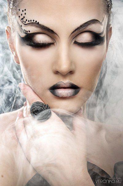 Black gems accent artistic fantasy makeup.