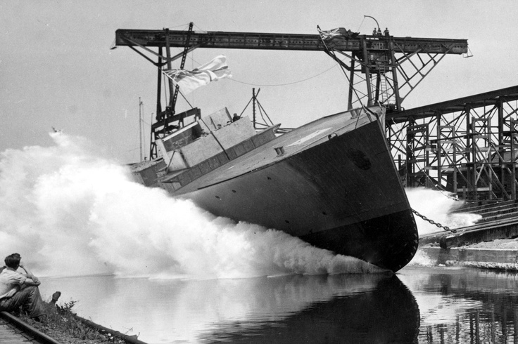 Ontario, Canada shipyards: HMCS Collingwood is launched on July 27, 1940. The ship's small displacement allows for sideways launch.