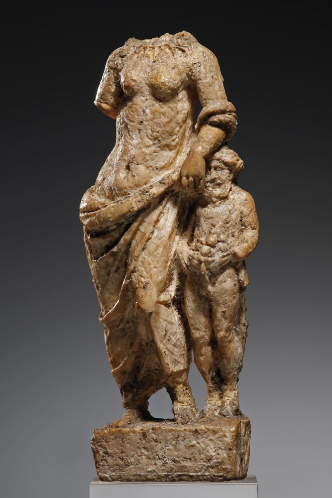 AN APHRODITE WITH PRIAPOS H. 5.9 cm. Bone Greek, Hellenistic, 3rd-1st cent. B.C. The goddess stands in a relaxed pose, a mantle draped around her waist on a rectangular base. She leans with the left arm on her son Priapos, who is characteristically depicted with an erect phallus and fruit. The precise and detailed rendition show that this is a high-quality piece. Head and right arm of Aphrodite lost.