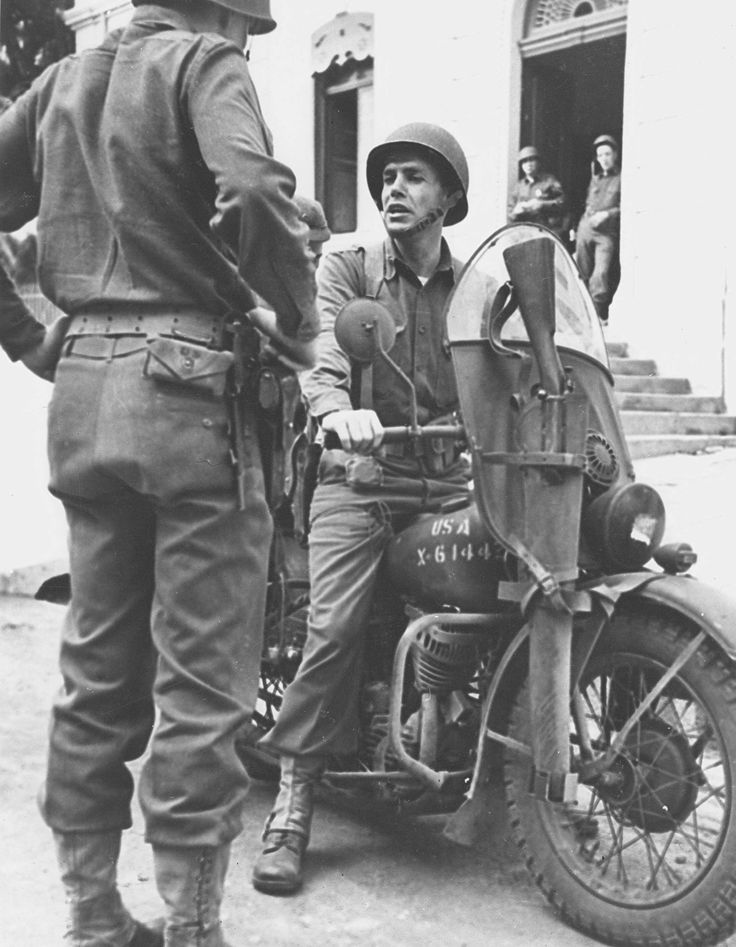 Battalion commander Lt Col William Darby rides his Harley, complete with saddle rifle scabbard holding his Springfield '03, and makes a stopover to talk with another officer. Unidentified North African location, 1942. US Army Harleys found their way into service with many Allied armies remaining in service well into the 1960s.