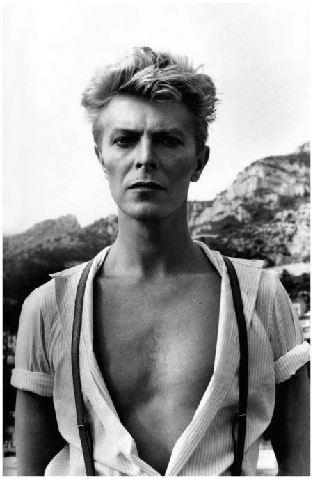 David Bowie in white and black by Helmut Newton. Shirt with lines opened as a v ... It was already eighties (1983 to be precise) but Bowie stays on this picture exactly like his music: an island apart.