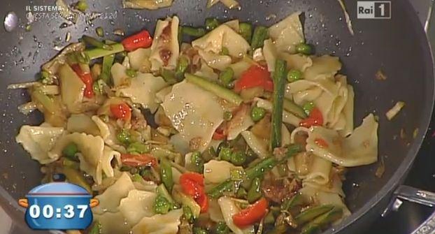 agliamo gli asparagi a pezzetti, tagliamo i carciofi a fettine dopo averli ben puliti.  Tagliamo anche le zucchine. In padella mettiamo un filo di olio con la pancetta e aggiungiamo gli asparagi e i carciofi, saltiamo e uniamo le zucchine, facciamo andare poi uniamo anche i pomodori e peperoncino, facciamo cuocere, saliamo.  Facciamo la pasta nel modo classico con farina e uova, impastiamo e stendiamo la sfoglia con la nonna papera. I fiori di zucca li usiamo crudi ma ben puliti per decorare…