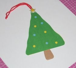 """Paper Christmas Tree Ornament with hole punched """"lights""""."""