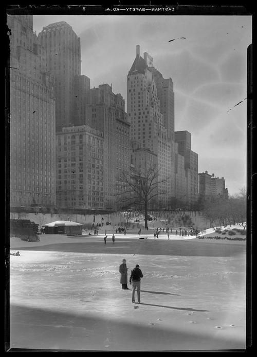 February 12, 1933  View of 59th Street and Fifth Avenue buildings seen from the Pergola in Central Park in snow.