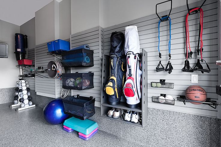 Sports equipment neatly organized on a garage wall using a slatwall system.