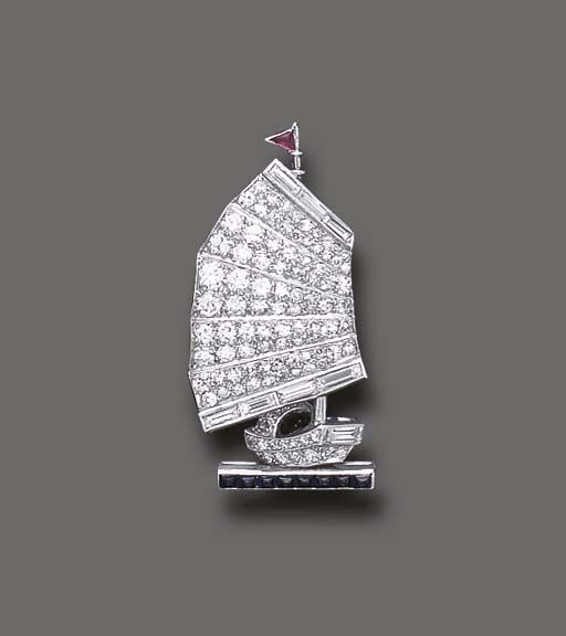 "AN ART DECO DIAMOND ""JUNK SHIP"" BROOCH c1925. Designed as a pavé-set diamond sailing junk, enhanced by baguette-cut diamond trim and calibré-cut sapphire and ruby accents, mounted in platinum."