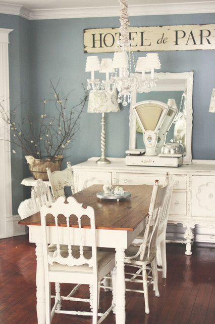 Love the quaintness of this smoky blue dining room with dark brown flooring!