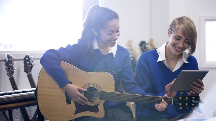 One girl in a school uniform plays guitar while looking at a tablet computer that a girl next to her is holding.