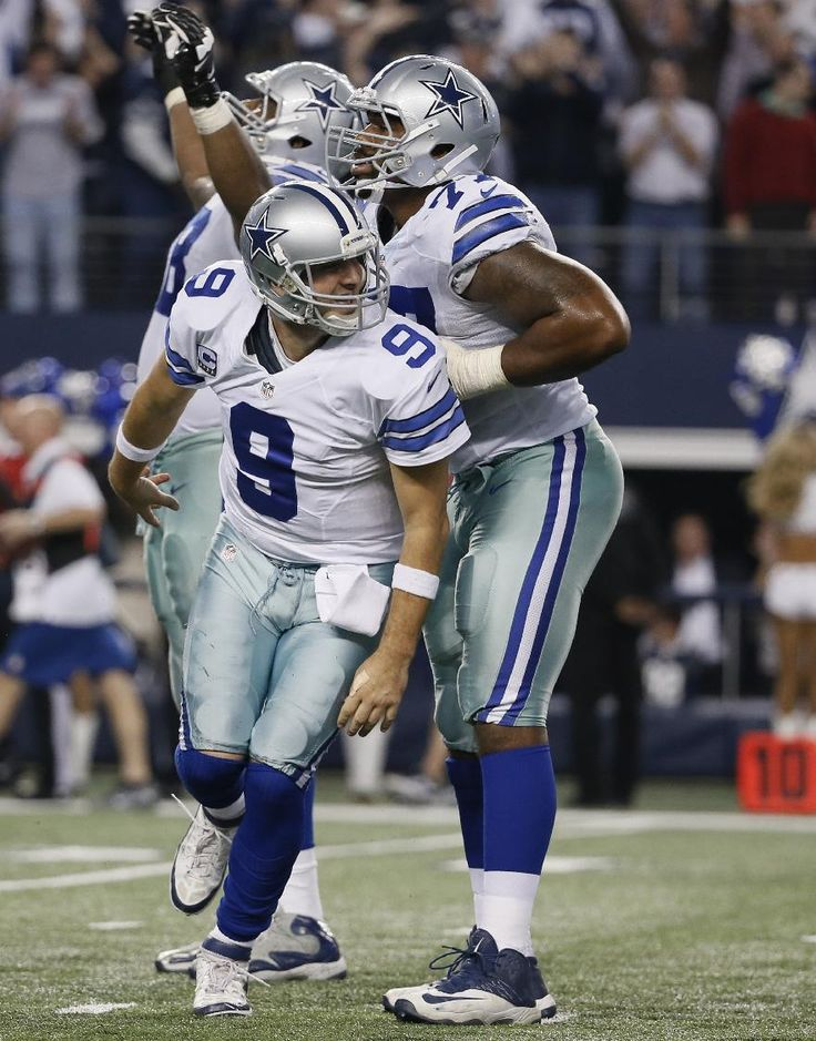 Dallas Cowboys quarterback Tony Romo (9) celebrates a touchdown against the Detroit Lions as tackle Tyron Smith (77) helps him up during the second half of an NFL wildcard playoff football game, Sunday, Jan. 4, 2015, in Arlington, Texas. (AP Photo/Tony Gutierrez)