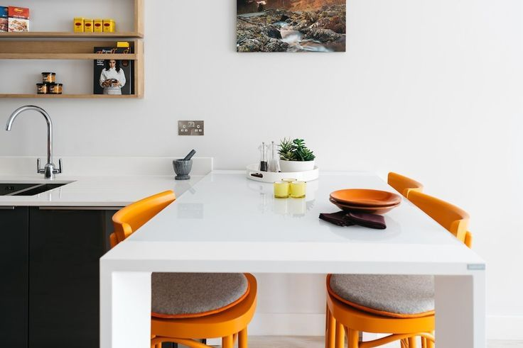 Dining area in an open plan kitchen with a modern glass bar table and stools
