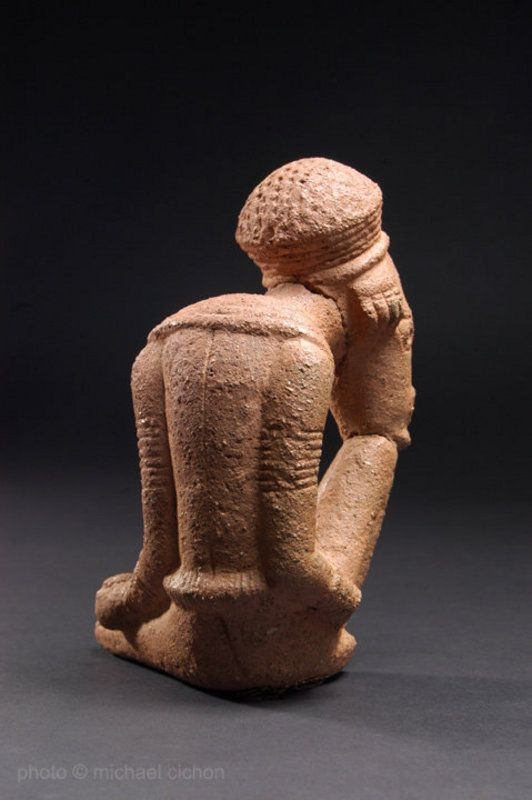 'The Thinker' figure, back view.