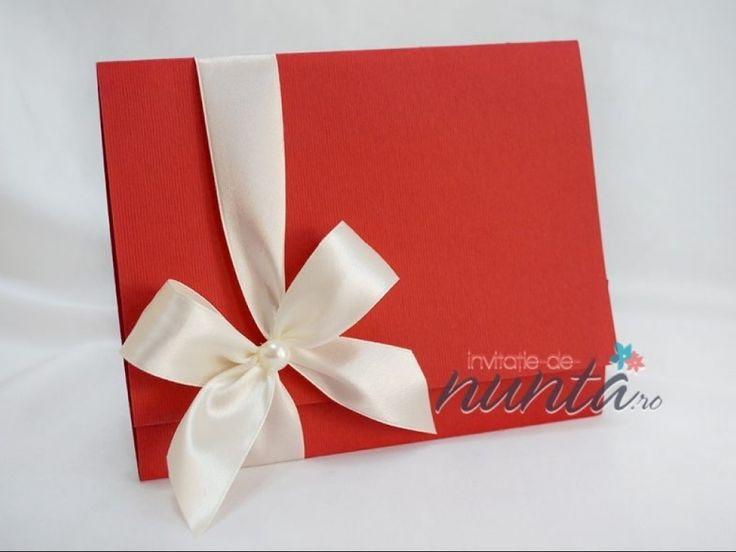 Invitatie de nunta eleganta, confectionata manual, din carton rosu. Textul invitatiei se tipareste in interior, pe un carton de culoare crem cu model floral. Invelitoarea rosie se pliaza in doua parti pe orizontala si se prinde cu o funda din panglica de culoare crem, cu perla. Dimensiuni: 16.5 x 14.5 cm Invitatia nu are si nu necesita plic. *Invitatia poate fi personalizata in functie de tematica si cromatica nuntii. COD: K027