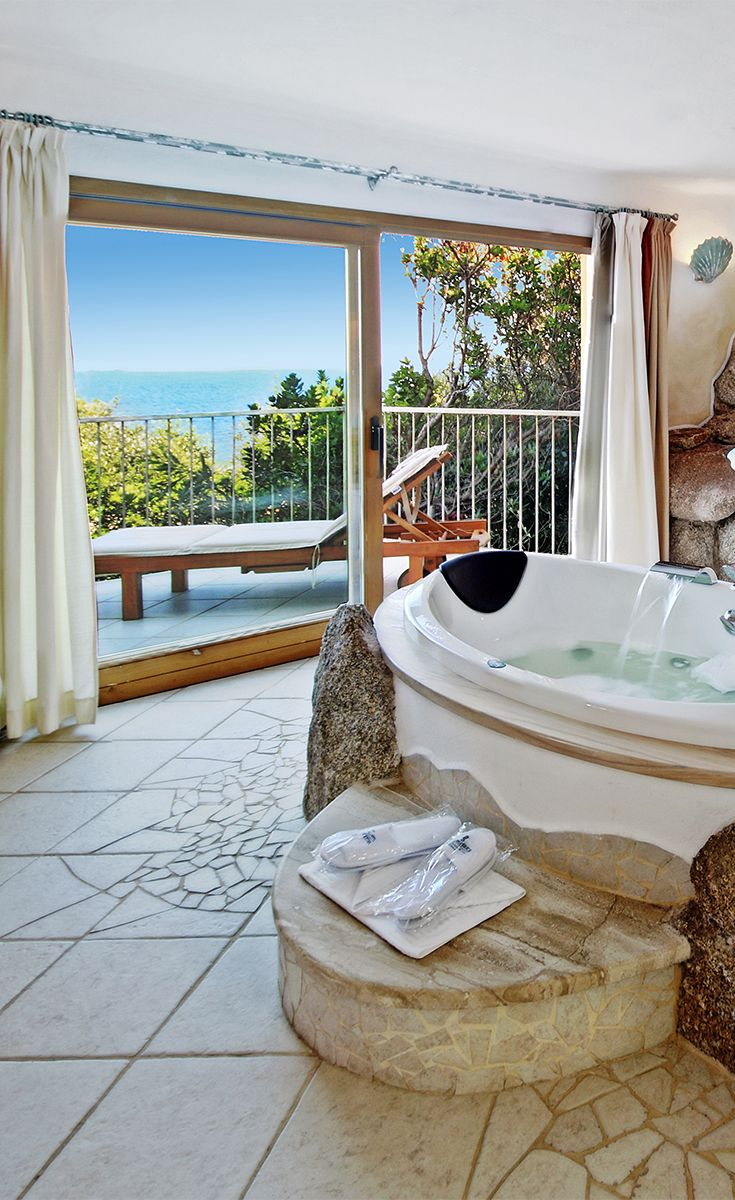 #Luxury #Room President Spargi #Sea #View - #Hotel Valle dell'Erica in #Sardinia. The island of #Spargi is right in front of you to delight you every time you wake up. The bathroom is a giant oasis of well-being that revolves around the bed for treatments and the Jacuzzi bathtub nestled between granite rocks.